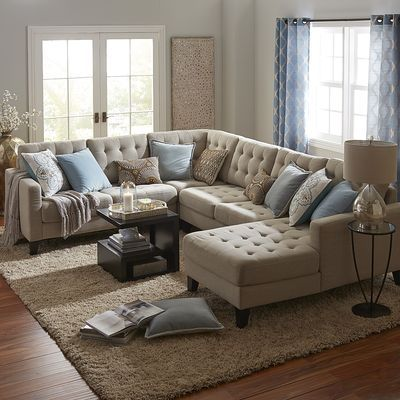 Hand-tufted and upholstered in a neutral poly/linen blend, our Nyle sectional has a modern, streamlined silhouette with tapered wood legs and loose cushions, and can be configured countless different ways. Coil springs in the seat cushions provide added comfort and support. Destined to become a classic.