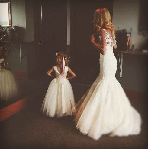 Mummy and daughter (bride and flower girl) looking in the mirror