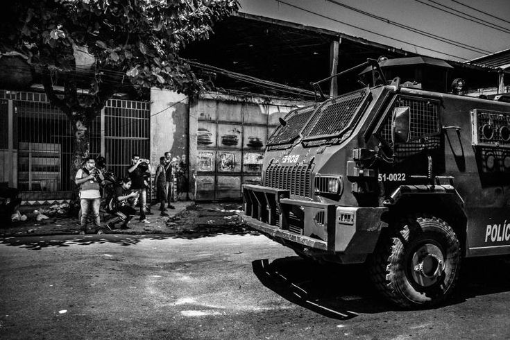 Daily Life, 3rd prize stories. Papo Reto collective members taking pictures and videos of the Special Police Forces tank car patrolling in the streets of Vila Aliança after a taxi driver was shot by police; Rio de Janeiro, Brazil, Feb. 8, 2015.
