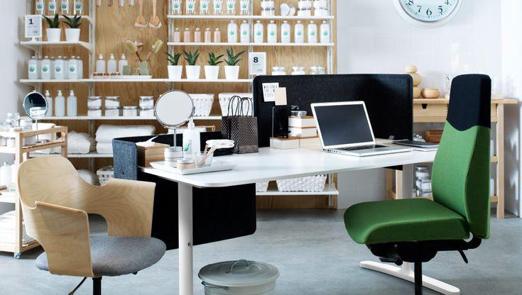 Офисный уголок с белым письменным столом и двумя креслами. На заднем плане – деревянный стеллаж с белыми полками, с экспозицией средств для ванн.