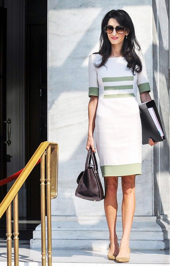 Amal Clooney in a structured white and green dress with accompanying olive green pumps.