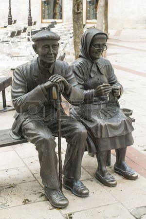Twee bronzen beelden die een oud echtpaar, man en vrouw in de dagelijkse activiteiten, rustend op een bankje photo