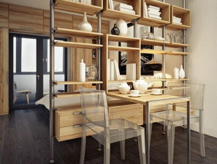 panneau de séparation, meuble avec des étagères en couleur claire, sol en parquet en couleur gris souris, table et deux chaises en matière transparente