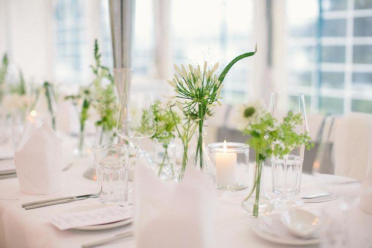 Puristische Tischdekoration mit unterschiedlichen Glasvasen und kleinen Sträußchen in Weiß und Grün bei www.weddingstyle.de | Foto: Henry Welisch Photography