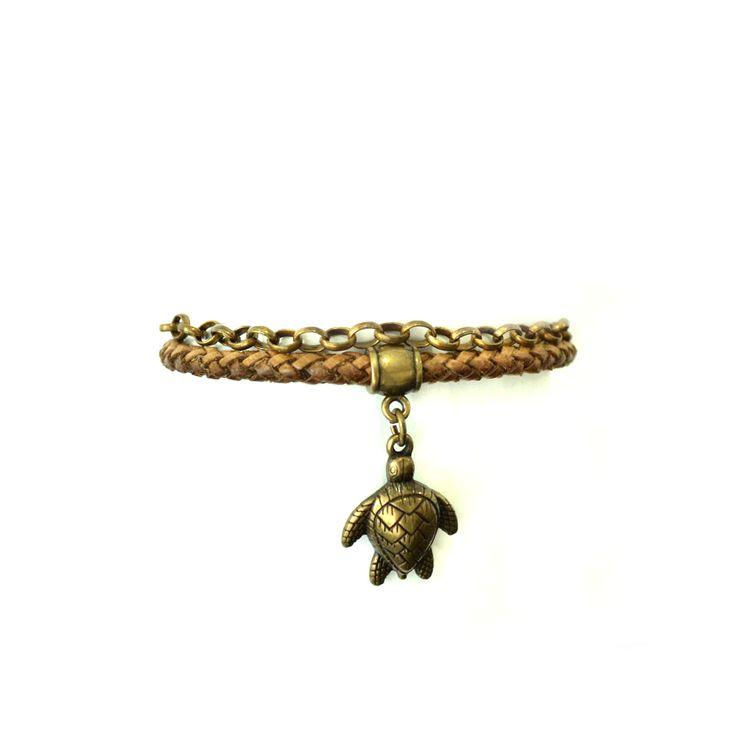 Pulseira feita em couro trançado e corrente de metal com pingente de tartaruga marinha em ouro velho. Esse acessórios é a cara do Verão carioca!