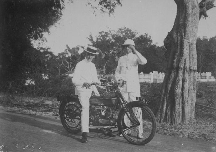 Europese mannen waarvan één op een motorfiets houden een praatje aan de kant van de weg waarbij op de achtergrond een kerkhof zichtbaar is 1915 (Collectie Tropenmuseum)