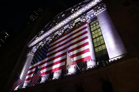 In this Friday, Feb. 17, 2017, photo, an American flag hangs on the front of the New York Stock Exchange. Global stock markets traded in fairly narrow ranges Tuesday, Feb. 28, as investors awaited a speech by President Donald Trump to both houses of Congress that could have a major bearing on the outlook for all types of financial assets in the near-term. (AP Photo/Peter Morgan)