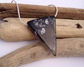 Clear charcoal grey eco-resin triangle icicle drop with silver foil and black swirl detail, on sterling silver snake chain.