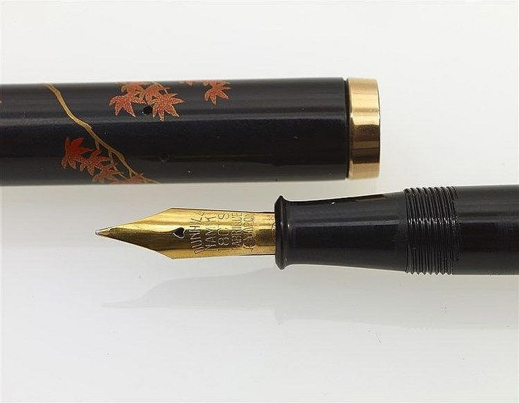 Stylo plume Dunhill Namiki des années 30 signé SHOMIN en laque urushi maki-é. Fabrication Japonaise des années 1930. Modèle flat top grade B avec un décor de poisson rouge et un capuchon bagué en or 18 cts, peint de branches fleuries, plume or 18 cts Dunhill Namiki moyenne et souple, remplissage par levier, a noter chose singulière le levier de compression est laqué, chose rare. Poisson en hira-maki-e de shu-urushi, grains d'argent et or 24 carats, plante aquatique kingyo-sô en hira-maki-e…
