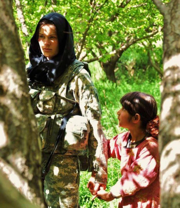 Une petite fille afghane prenant la main d'un soldat américain