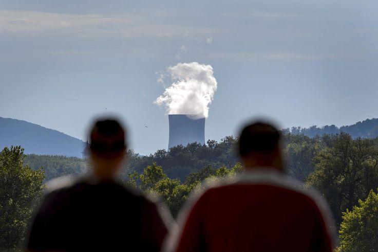 15.09 Deux personnes contemplent la tour de refroidissement de la centrale nucléaire de Gösegen, dans le canton de Soleure.Photo: AFP/Fabrice Coffrini