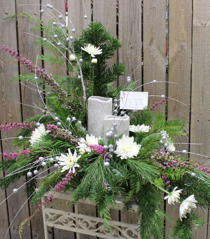 Fresh flower arrangement with Christmas greens and silver glitter LED candles