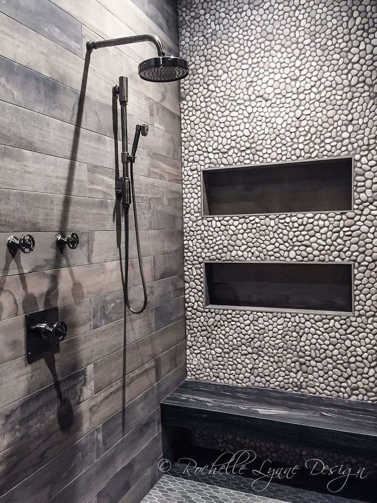 Wood look tile and pebbles in shower, bench seat of stone, large shower niches…