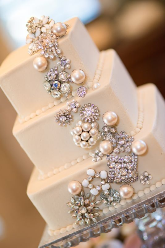 A simple & gorgeous white cake decorated with pearls & crystal brooches. <3