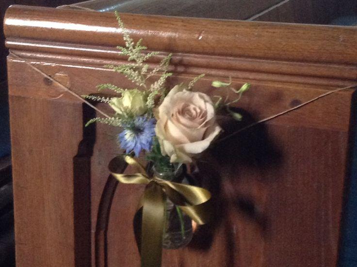 Pew ends using quicksand rose, nigella in blue, astilbe, olive ribbon in a mini milk bottle.