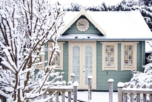 winter cottage.  There is something about small spaces that is intriguing.  Makes me wonder what this house looks like on the inside.  Love the clock on the dormer, the arched door panes, snow covered fence posts.  Wish they had posted an interior shot.