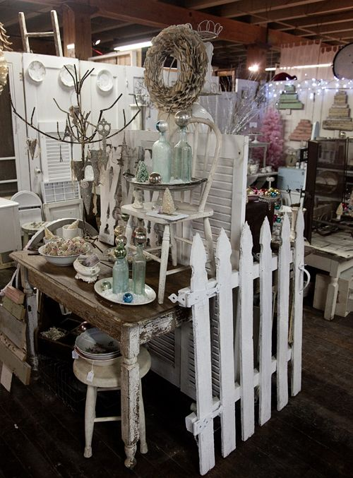 bottles and bulbs, book page wreath, wooden trees in background, use of fence and shutters to define the display. Very cute!  And doors as wall in back.