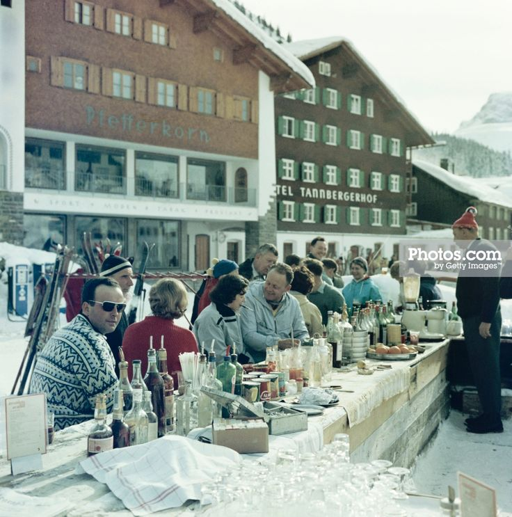 The Ice Bar at the Hotel Krone in Lech, Austria, 1960. The Hotel Pfefferkorn and Hotel Tannbergerhof are in the background. Photo by Slim Aarons. Add the party to your walls as a framed photo print.