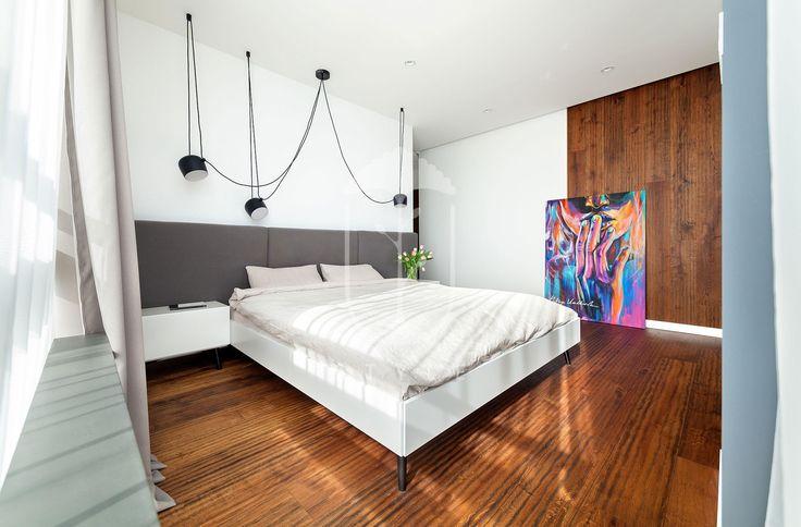 Натуральное дерево на полу и частично на стене, белые стены, контрастные черные светильники, придуманные братьями Буррулек и белая кровать с серым изголовьем - вот и все элементы, формирующие интерьер спальни.
