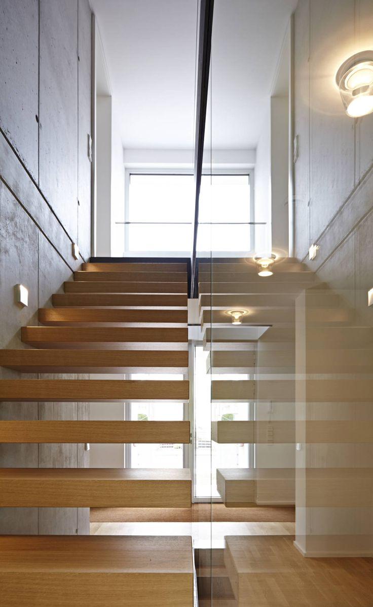 schwebende Treppenstufen an einer Sichtbetonwand mit Glasabtrennung : Moderner Flur, Diele & Treppenhaus von Marcus Hofbauer Architekt