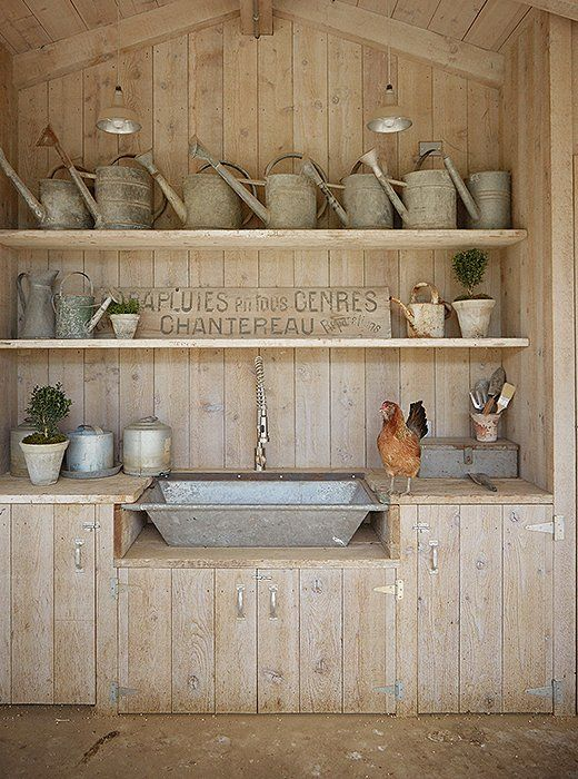 """A small kitchen in the coop has a galvanized sink made from a vintage trough. """"I store all of my kitchen and chicken supplies here,"""" says Brooke. The vintage metal watering cans come from their frequent trips to flea markets and antiques shops."""