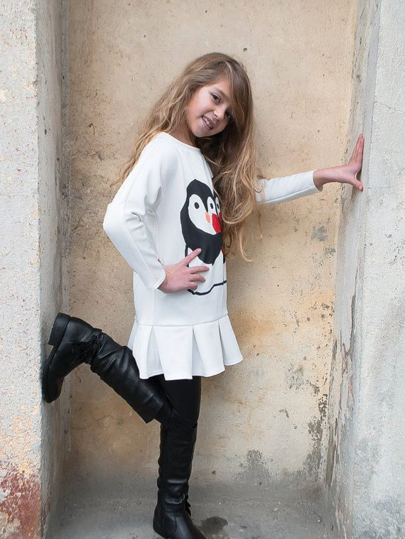 Casual neoprene knee length girls white dress for spring and winter with printed penguin long sleeved dress without collar and trendy silhouette.  This white long sleeved dress is for 2 3 4 5 6 7 8 9 and 10 years old girls.  There are no buttons or zipper on this kids dress. It has a painted penguin drawing.  Because of its stylish silhouette it is suitable for both, formal events and spring winter clothing.  This toddler girls white neoprene dress can also be worn under jackets, cardigans…