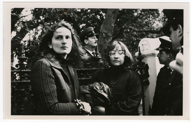 Photograph of Cornelia Bullen-Smith (on left) and Beva Runciman, who chained themselves to the gates of Parliament in protest against the death of a child in detention. They are watched by three policemen. From the Black Sash collection of photographs and documents.