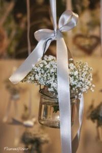 Particolare di composizioni di gipsofila in piccoli vasi per nozze