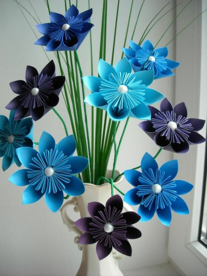 summer diys, several paper origami flowers in violet and blue, decorated with white pearl pins, with sharp green paper leaves, placed in white ornate vase