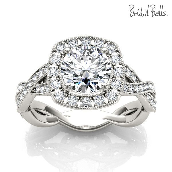 Cushion Halo 1.33cttw Diamond Engagement Ring with Crossed Shank. This stunning low diamond halo style features 1/3cttw of round accent diamonds, surrounding a 1ct center diamond. Features a large cus