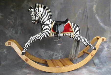 The zebra has a bright red saddle blanket with a gold trim complementing the zebra's stripes on a natural oak bow. The zebra is available on bow or safety stand.