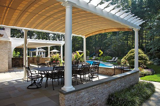 A curved-top pergola offers the option of extending fabric just beneath the structure to increase the amount of shade. The curved details suit the more traditional architecture of the house. Photo: Walpole Woodworkers