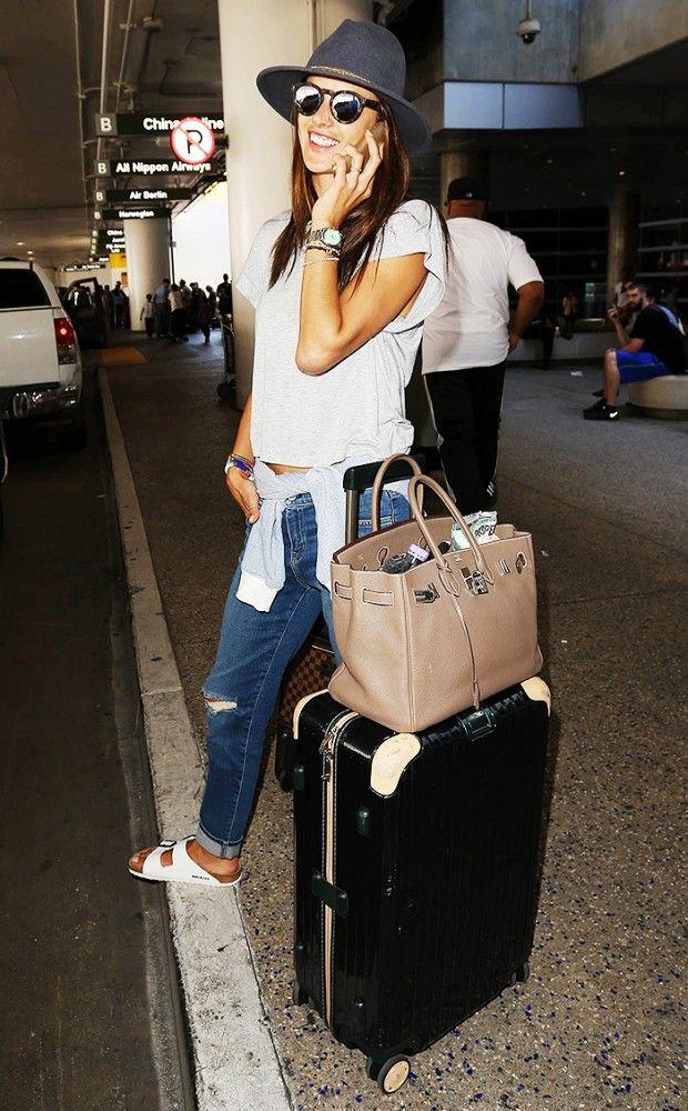 Alessandra Ambrosio wears a gray t-shirt, distressed jeans, Birkenstocks, mirrored sunglasses, a fedora, and an Hermes Birkin bag