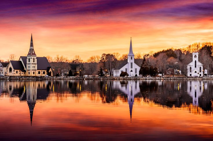 Three churches stand along the waterfront in Mahone Bay, Nova Scotia Canada with the sky on fire behind them.