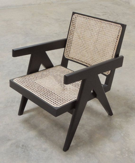 A contemporary handcrafted re-edition of the Easy Armchair, a lounge chair model designed by Pierre Jeanneret. The teak wood is stained black and a layer of melamine applied on top to give it an opaque black finish. Materials Used Teak (Tectona Grandis) and natural cane.  Dimensions H 70.0 cms x W 57.0 cms x D 71.5 cms (H 27.5 in x W 22.4 in x D 28.1 in) Seat Height: 36.2 cms (14.25 in) Arm Height: 58.0 cms (22.8 in)  Design Period c. 1955-56  Notes Our Easy Armchair re-edition evolved over…