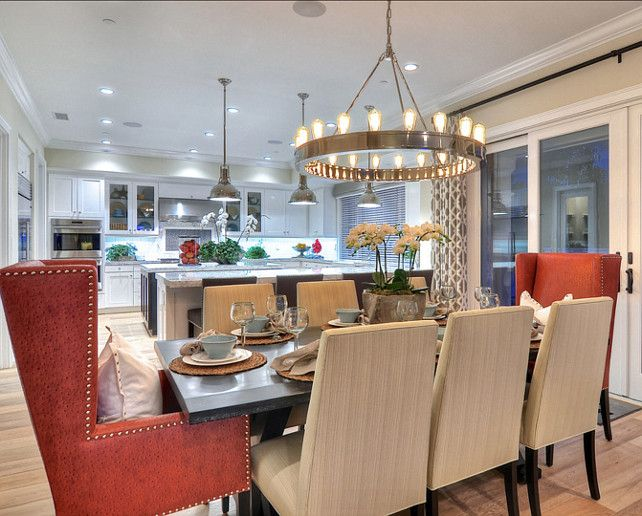 Dining Room Ideas.  Eight upholstered chairs, including two terracotta colored arm chairs, surround this large dining table.   Details A Design Firm   Newport Hills, Ca