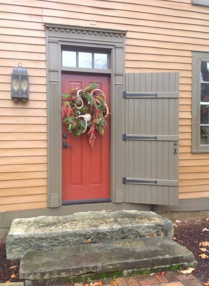 Red colonial door with mustard siding and grey-green trim.