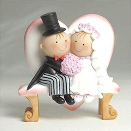 """Complementos de boda: bonita figura para la tarta de bodas de la colección """"Pit y Pita"""" en la que la parejita aparece sentada en un banco con forma de corazón."""