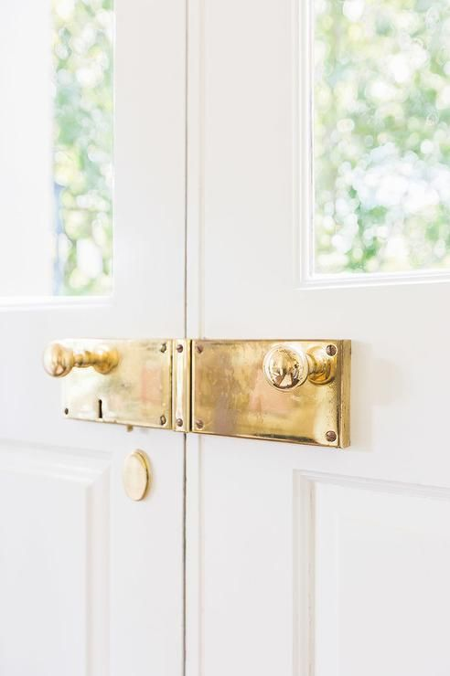 Alyssa Rosenheck - Katie Gibson Interiors - Chic home boasts white double front door fitted with glass panes adorned with polished brass door knobs and hardware.