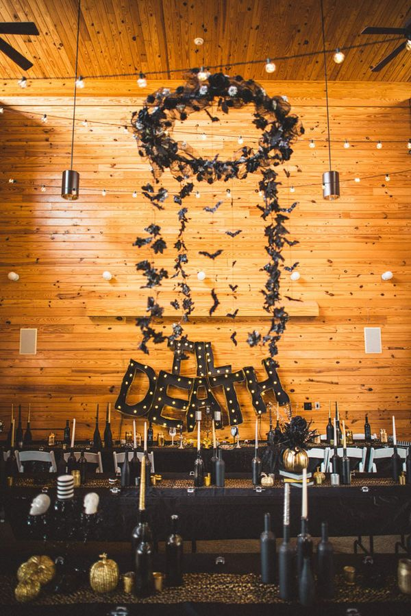 As you can see from this phenomenal chandelier, you can be both spooky and chic with your Halloween wedding details. This couple created a bat chandelier in front of their head table, with a new spin on marquee signage.