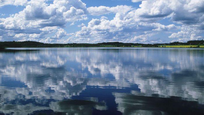 Pilvet kuvastuvat tyyneen järven pintaan.