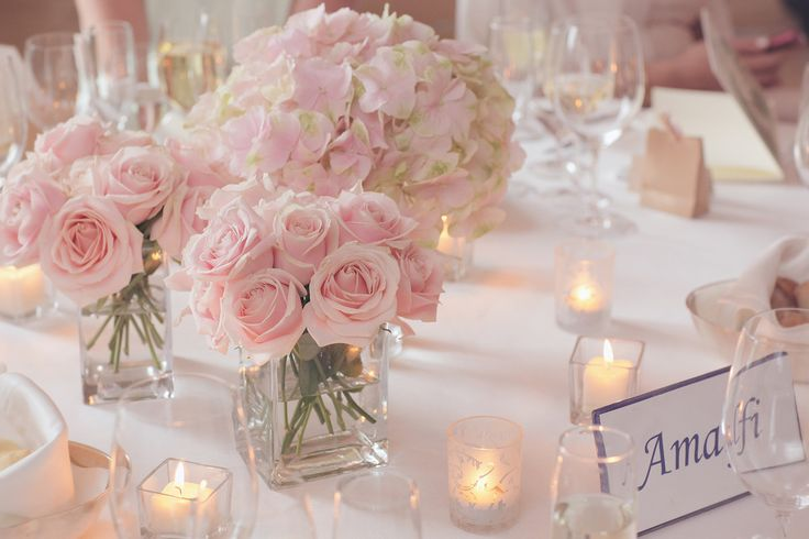 Square glass vases were filled with pink roses and were used as centerpieces. Venue: Belmond Hotel Caruso Event Coordinator: The Amalfi Experience Floral Design: Armando Malafronte
