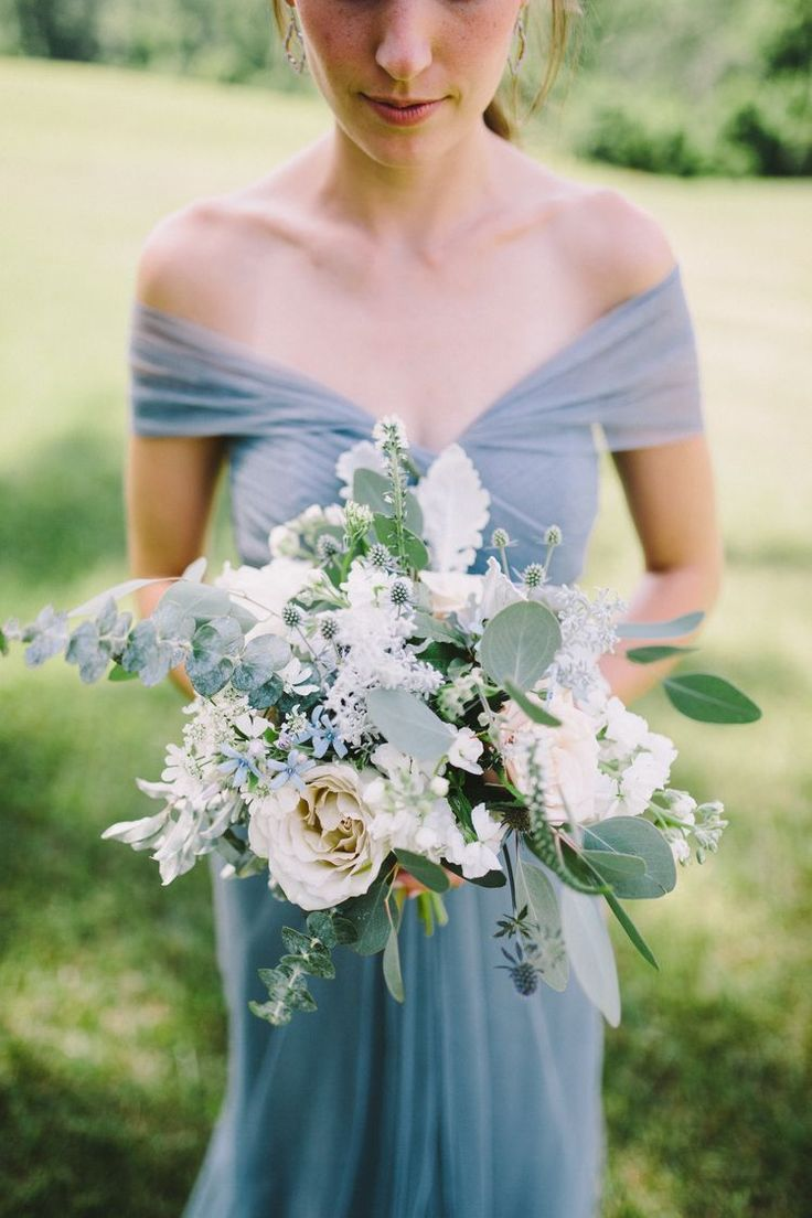 Wilder form ... Eucalyptus,soft cream roses, blue thistle, tweedia, dusty miller, and kochia are all included in this icy bridesmaids bouquet.  Cream & Dusty Blue Summer Real Wedding — Flowers by Petal Flower Company, photo by Tyler Phenes.