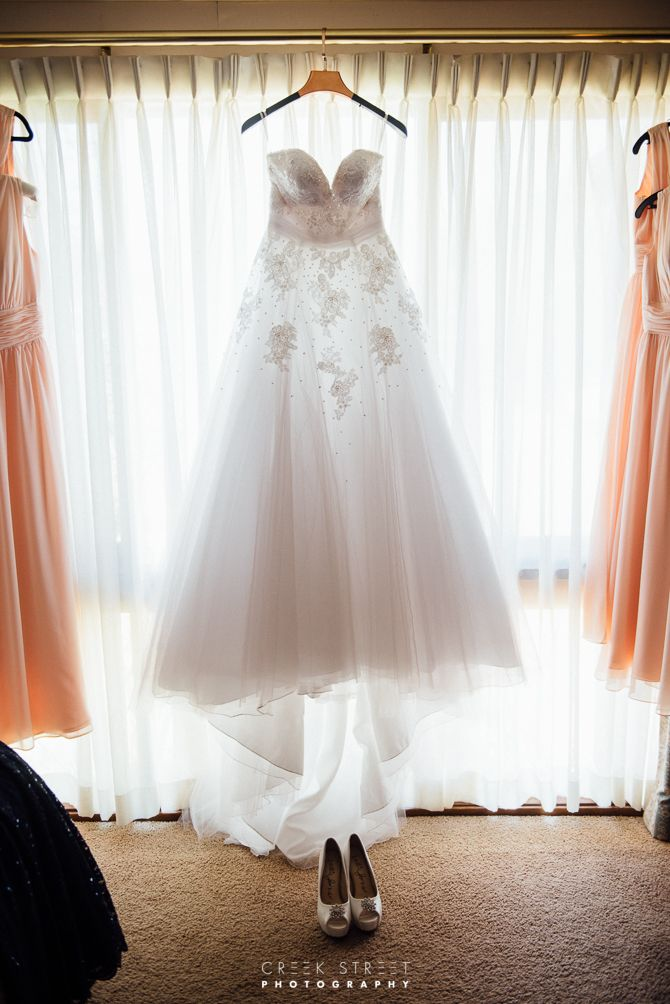 bride getting ready - wedding gown in window