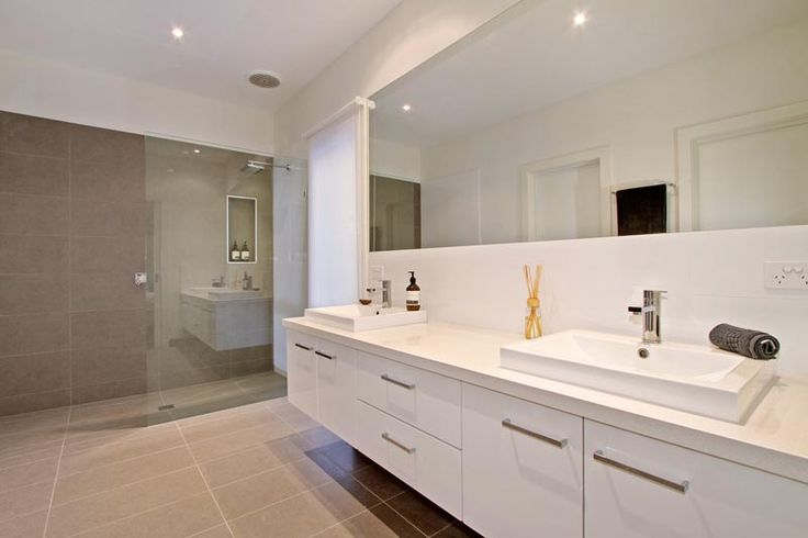 It's all about the detail within this spacious bathroom. The organic coloured tiles are a perfect match with the clean lined cabinetry and large open shower.