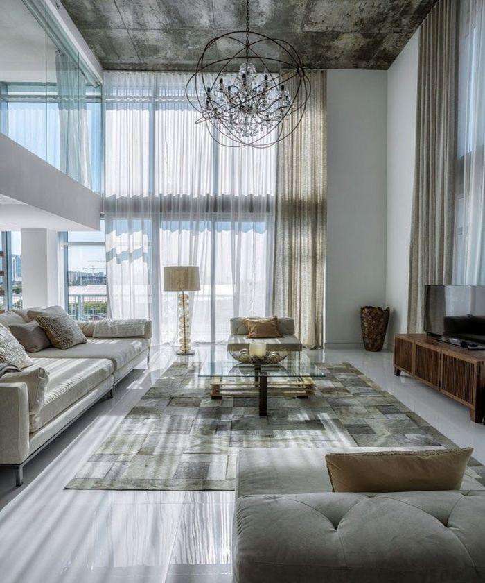 Estancia con un altísimo techo de hormigón desnudo y largas cortinas de lino.