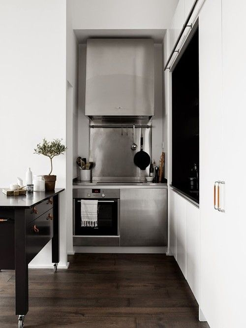 Small Kitchen But Efficient A Stylish Mixture Of Polished Wood White And Stainless Steel