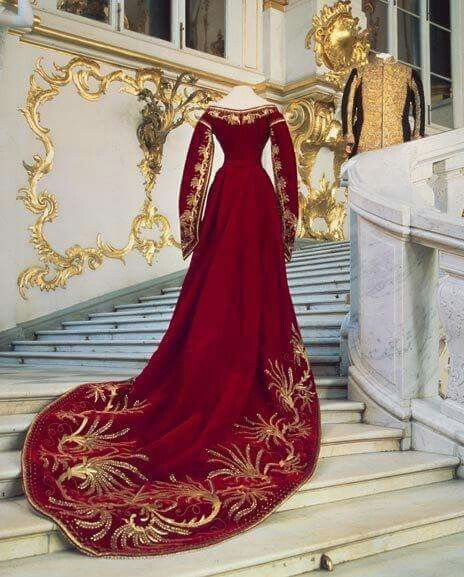 Vestido que pertenceu à czarina Maria Feodorovna, esposa do czar Alexandre III e mãe de Nicolau II. A peça é composta em veludo carmesim e bordada a fios de ouro. À frente, podemos ver um traje que pertenceu ao próprio Alexandre. As roupas foram dispostas de forma a simular um encontro entre o casal de imperantes.