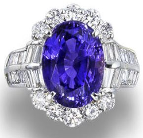 A colour-changing sapphire and diamond ring.  Set with an oval-cut colour-changing sapphire, measuring 10.86 carats, partially framed by round brilliant-cut diamonds, flanked by tapered baguette-cut diamonds, between shoulders set with baguette-cut diamonds, mounted in platinum, the diamonds estimated to weigh approximately 2.50 carats in total, ring size 6½. Via Bonhams.