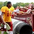 Washington Redskins quarterback Robert Griffin III (10) shakes hands with fans while walking off the field after a training camp practice at Redskins Park on July 30, 2013.